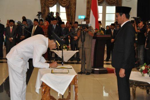 Bupati Hendrajoni menandatangani surat berita acara serah terima disaksikan Gubernur Irwan Prayitno.